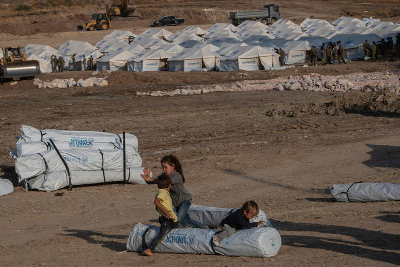Children play as Greek soldiers install tents at a temporary camp near Mytilene town, on the northeastern island of Lesbos, Greece, Saturday, Sept. 12, 2020. Greek authorities have been scrambling to find a way to house more than 12,000 people left in need of emergency shelter on the island after the fires deliberately set on Tuesday and Wednesday night gutted the Moria refugee camp. (AP Photo/Petros Giannakouris)