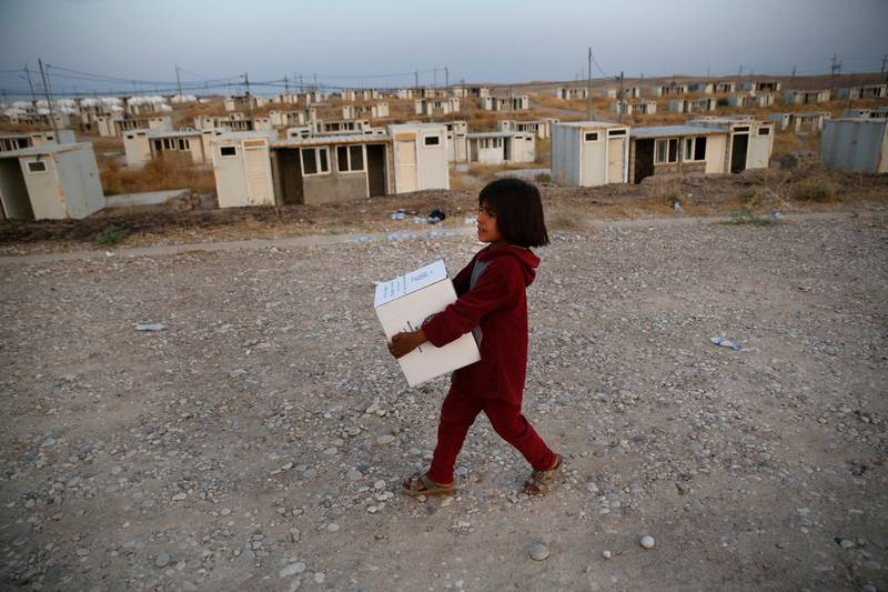 A Syrian girl who was displaced by the Turkish military operation in northeastern Syria, carries a box of food supplies at the Bardarash refugee camp, north of Mosul, Iraq, Thursday, Oct. 17, 2019. Hundreds of refugees have crossed into Iraq in the past week, mostly through unofficial border points. On Wednesday, a first group of 890 people were bused to the Bardarash camp, in northern Iraq's semi-autonomous Kurdish region, which up until two years ago housed displaced people from the Iraqi city of Mosul. (AP Photo/Hussein Malla)