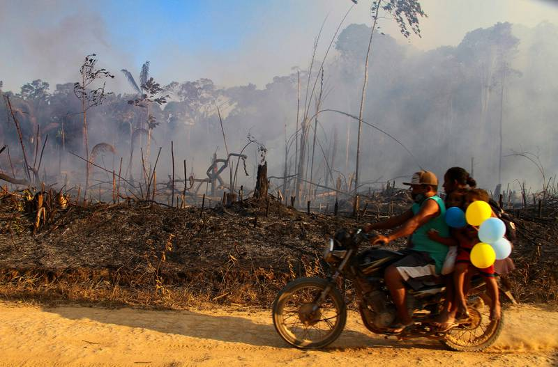 A family rides along a paved dirt road in an area scorched by fires near Labrea, Amazonas state, Brazil, Friday, Aug. 7, 2020.  According to the National Institute for Space Research, fires in the Brazilian Amazon increased 28% in July from a year ago. Environmentalists have expressed concern at the rise because August traditionally marks the beginning of the fire season in the region. (AP Photo/Edmar Barros)