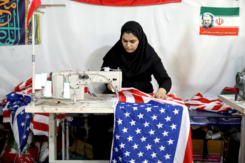 In this Saturday, Feb. 8, 2020 photo, a worker sews a U.S. flag at the Diba Parcham Khomein factory in Heshmatieh village, a suburb of Khomein city, in central Iran. Her work is destined to go up in smoke. This factory serves as a major producer for the American and Israeli flags constantly burned at demonstrations in the Islamic Republic. (AP Photo/Ebrahim Noroozi)