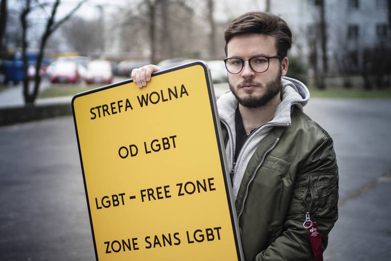 """FILE - In this Jan. 24, 2020 file photo, Bart Staszewski, an LGBT activist, holds up a sign he uses to protest anti-LGBT resolutions, in Warsaw, Poland. The European Parliament is due to debate a resolution that would symbolically declare the entire 27-member European Union to be a """"freedom zone"""" for LGBT people. The resolution comes largely in reaction to developments over the past two years in Poland, where many local communities have adopted largely resolutions declaring themselves to be free of what Polish conservative authorities have controversially dubbed """"LGBT ideology."""" (AP Photo/ Przemys?aw Stefaniak, File)"""
