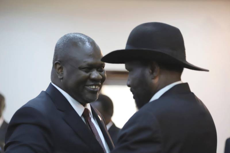 The president of South Sudan, Salva Kiir Mayardit, right, and Dr. Riek Machar, left, greet each other after swearing in ceremony in Juba, South Sudan Saturday, Feb. 22, 2020. South Sudan opened a new chapter in its fragile emergence from civil war Saturday as rival leaders formed a coalition government that many observers prayed would last this time around. (AP Photo)