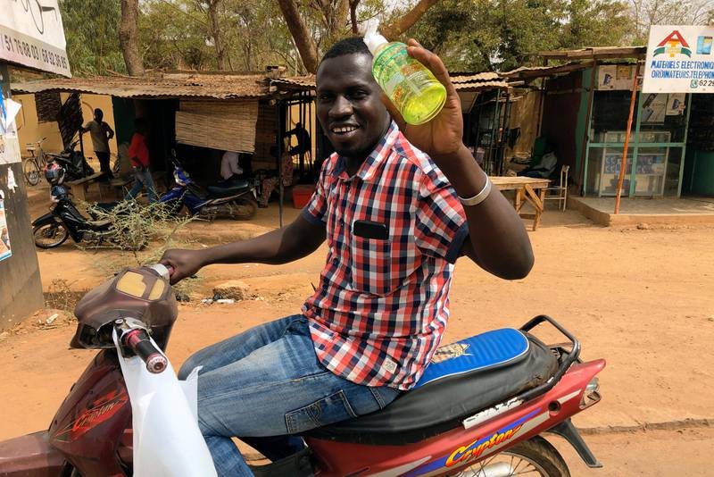 In this photo taken Friday March 20, 2020, a man tries selling hand sanitizer from his motorbike while driving around Burkina Faso's capital, Ouagadougou.  For many people the virus causes mild or moderate symptoms but for others it can cause severe illness, especially in older adults and people with pre-existing health problems. (AP Photo/Sam Mednick)