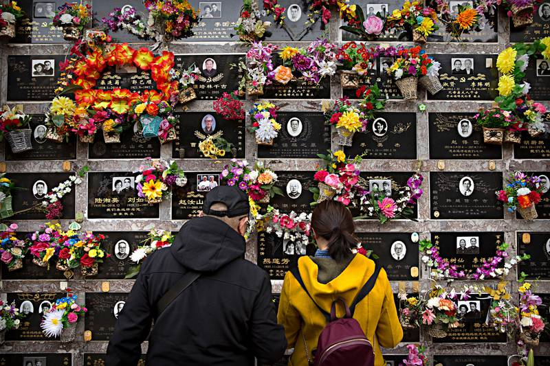 Visitors look at a columbarium at the Babaoshan Revolutionary Cemetery during the Qingming festival in Beijing, Friday, April 5, 2019. Qingming festival, also known as the Grave Sweeping Day, is a day when Chinese around the world remember their dearly departed and take time off to clean up the tombs and place flowers and offerings. (AP Photo/Mark Schiefelbein)