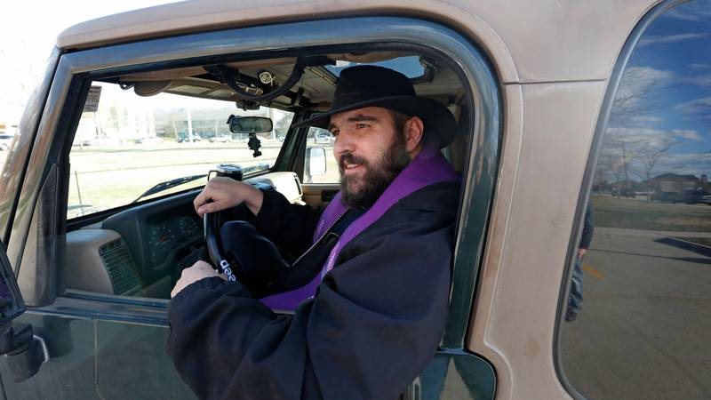"""Father Stephen Tilley sits behind his steering wheel during the """"Meet Me at the Jeep,"""" for a drive-up confession at Skaggs Catholic Center, Sunday, March 22, 2020, in Draper, Utah. With the threat of the new coronavirus closing churches, some Catholic priests in Utah offered to hear drive-up confessions. (AP Photo/Rick Bowmer)"""