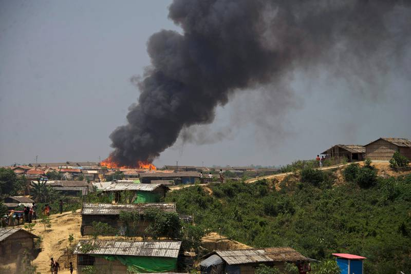 Smoke and flames rise from the site of a fire at  the Kutupalong refugee camp in Cox's Bazar, Bangladesh, Wednesday, April 24, 2019. A fire raced through a sprawling camp of Rohingya refugees in southern Bangladesh, destroying more than two dozen huts and a mosque on Wednesday, an official said. (AP Photo)