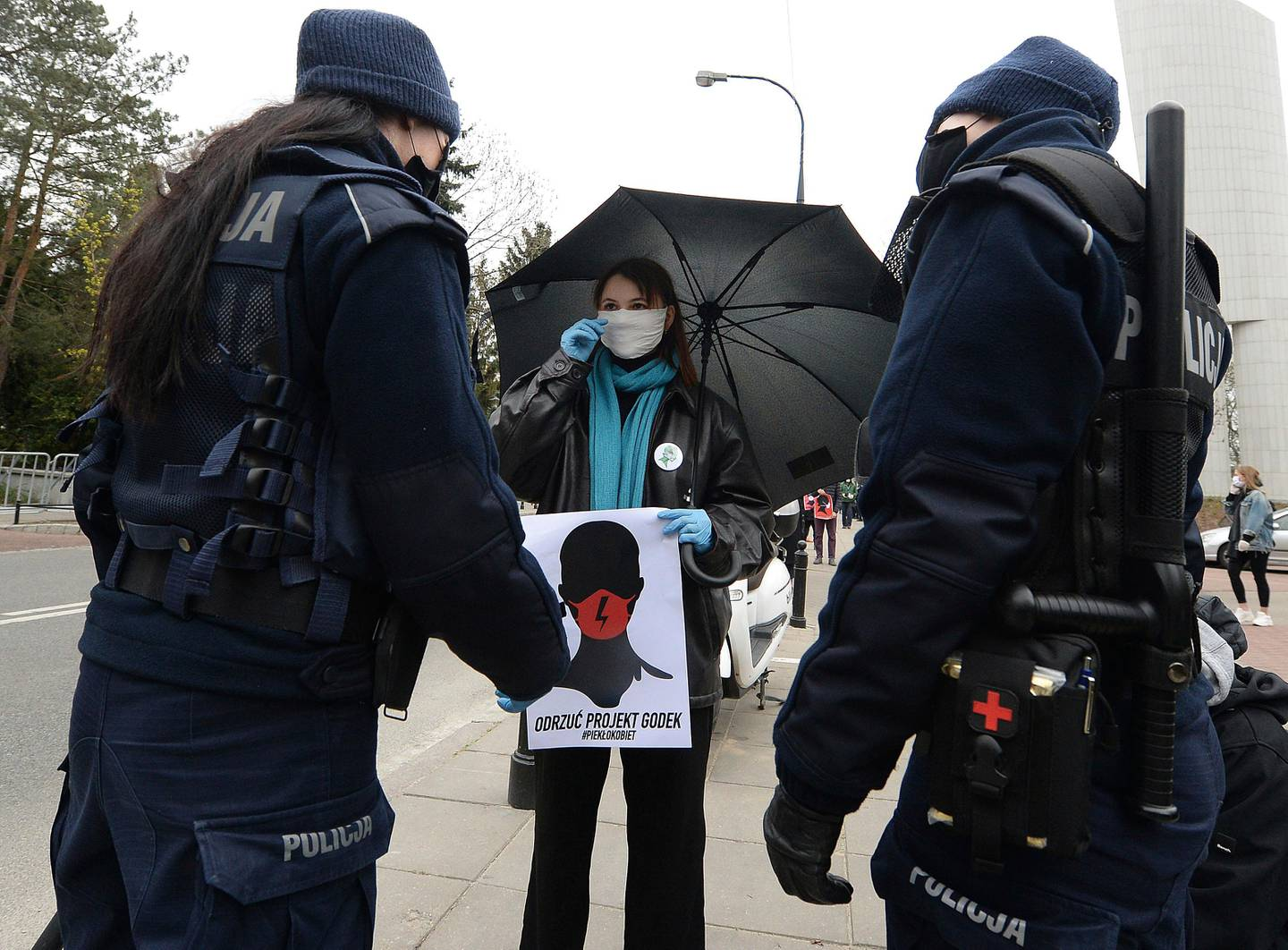 A women's rights activist, wearing a mask against the spread of the coronavirus, protests against a draft law tightening Poland's strict anti-abortion law near the parliament that was debating the draft law, in Warsaw, Poland, on Wednesday, April 15, 2020. (AP Photo/Czarek Sokolowski)