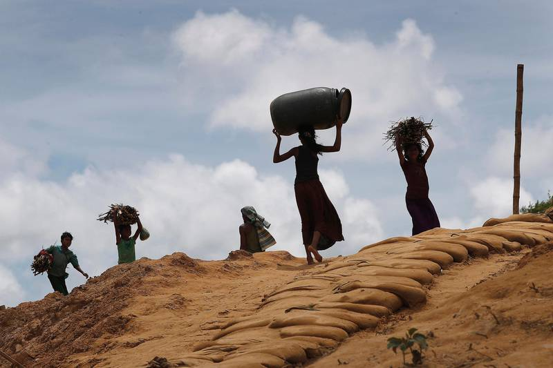 Rohingya girls carry firewood on the heads as they make their way through Kutupalong refugee camp, Thursday, June 28, 2018, in Bangladesh. (AP Photo/Wong Maye-E)