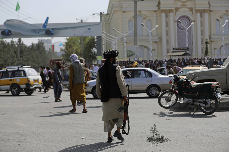 Taliban-krigere holder vakt foran flyplassen i Kabul mandag. Det oppsto kaotiske scener da flyplassen ble fylt menneskemengder som frykter Taliban og prøver å komme seg ut av landet. Foto: Rahmat Gul / AP / NTB