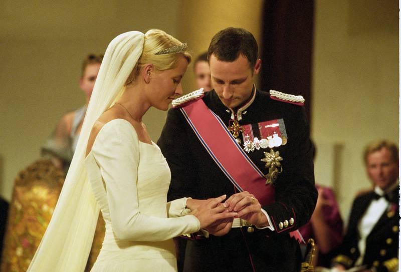 Kronprins Haakon og kronprinsesse Mette-Marit ble viet av biskop Gunnar Stålsett i Oslo domkirke lørdag 25. august. Her setter kronprinsen gifteringen på kronprinsessens finger.  Foto: Bjørn Sigurdsøn / NTB