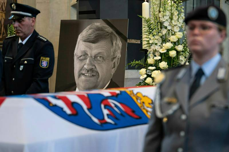 FILE-In this June 13, 2019 file photo a picture of Walter Luebcke stands behind his coffin during the funeral service in Kassel, Germany. Germany's top security official says the far-right extremist suspected in the killing of a politician from Chancellor Angela Merkel's party has told authorities that he acted alone. Walter Luebcke, who led the Kassel regional administration in central Germany, was fatally shot in the head at his home on June 2. (Swen Pfoertner/dpa via AP)