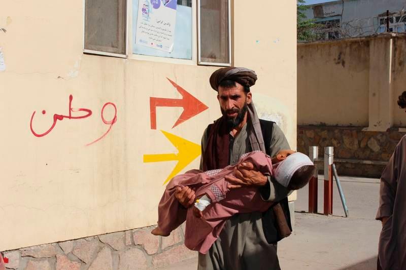 En sivil afghaner bærer et såret barn til sykehus etter at det ble såret i forbindelse med kamper mellom Taliban-opprørere og regjeringsstyrker i provinsen Badghis tidligere denne uka. Foto: Mirwis Omari / AP / NTB