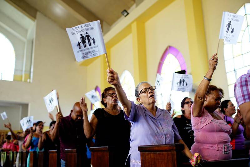 """Worshippers wave paper flags that read in Spanish """"I am in favour of the original design. The family as God created it. Wedding between man and woman"""", during a service at a Methodist Church in Havana, Cuba, October 4, 2018. Picture taken on October 4, 2018. REUTERS/Alexandre Meneghini"""
