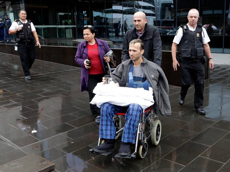A man in a wheelchair is escorted from outside the High Court in Christchurch, New Zealand, Friday, April 5, 2019. A New Zealand judge has ordered that the man accused of killing 50 people at two New Zealand mosques, 28-year-old Brenton Harrison Tarrant, undergo two mental health tests to determine if he's fit to enter pleas in the case. (AP Photo/Mark Baker)