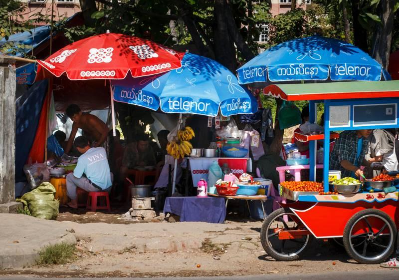 YANGON, MYANMAR 20141202. Telenor har teppelagt gatene i Myanmars hovedstad Yangon med blå bannere, parasoller og skilt med synlig Telenor logo.  Foto: Heiko Junge / NTB
