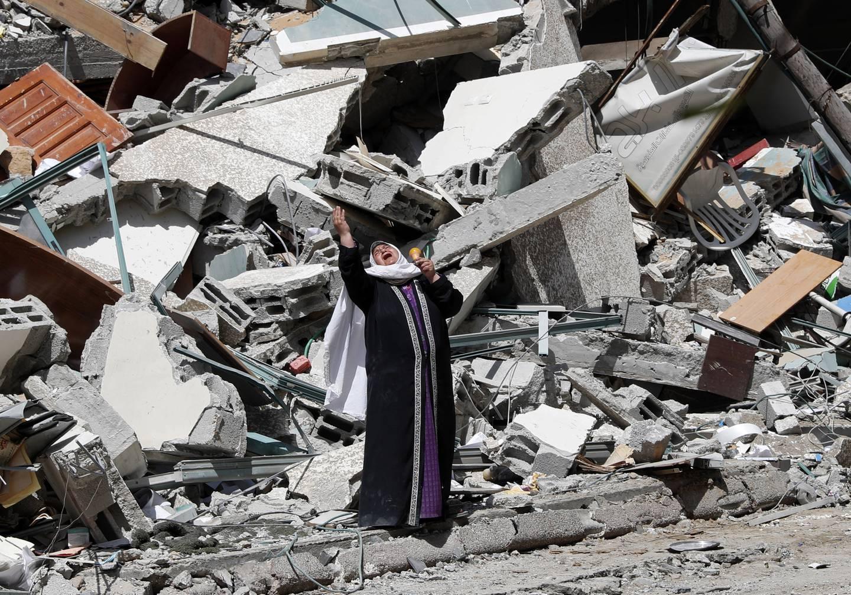 En kvinne i sorg ved siden av en bygning som ble ødelagt av et israelsk luftangrep på Gazastripen søndag. Foto: Adel Hana / AP / NTB