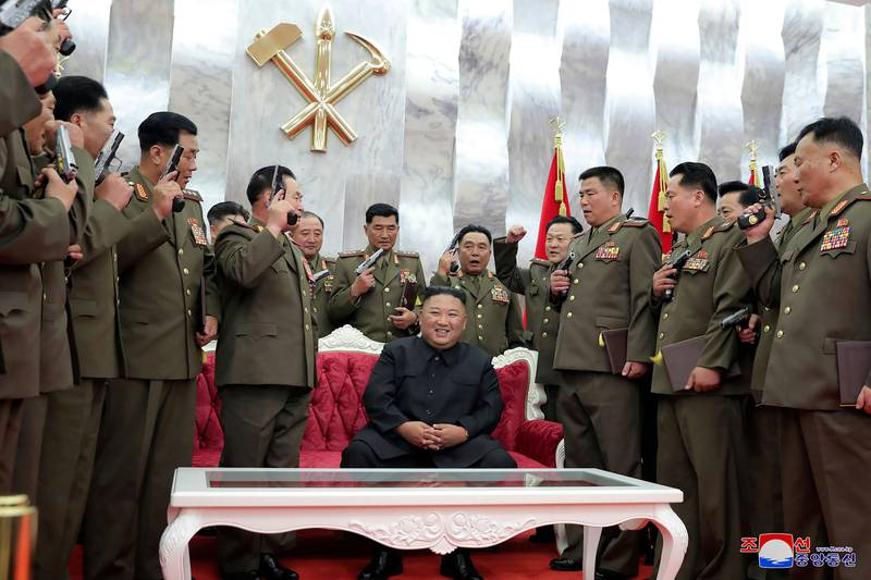 """In this Sunday, July 26, 2020, photo released by the North Korean government, North Korean leader Kim Jong Un, sitting, is surrounded by senior military officials holding """"Paektusan"""" commemorative pistols they received from Kim during a ceremony in Pyongyang, North Korea. Independent journalists were not given access to cover the event depicted in this image distributed by the North Korean government. The content of this image is as provided and cannot be independently verified. Korean language watermark on image as provided by source reads: """"KCNA"""" which is the abbreviation for Korean Central News Agency. (Korean Central News Agency/Korea News Service via AP)"""