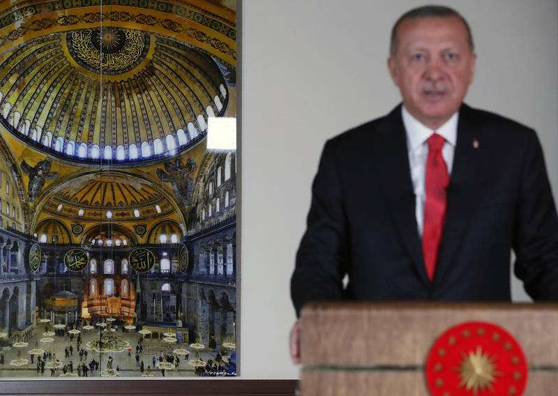 Turkey's President Recep Tayyip Erdogan, backdropped by a photograph of the Byzantine-era Hagia Sophia, one of Istanbul's main tourist attractions, delivers a televised address to the nation, in Ankara, Turkey, Friday, July 10, 2020. Erdogan formally reconverted Hagia Sophia into a mosque and declared it open for Muslim worship, hours after Turkey's highest administrative court annulled a 1934 decision that had made the religious landmark a museum. (Presidential Press Service via AP, Pool)