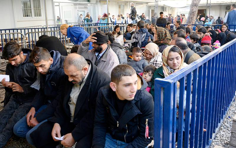Newly arrived migrants wait to be seen by authorities at Moria refugee camp on the northeastern Aegean island of Lesbos, Greece, Wednesday, Nov. 27, 2019. Last week Greece's conservative government announced plans to overhaul the country's migration management system, replacing existing open camps on the islands with detention facilities and moving 20,000 asylum seekers to the mainland over the next few weeks. (AP Photo/Ignatis Tsiknis)
