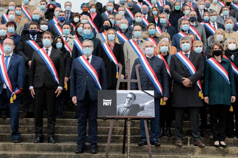 French lawmakers observe a minute silence to pay tribute to slain teacher Samuel Paty, Tuesday, Oct.20, 2020 on the steps of the National Assembly in Paris. A memorial march will be held Tuesday evening near Paris in homage to the history teacher who was beheaded last week, while French police said 16 people remain in custody as part of the investigation into the attack. (AP Photo/Lewis Joly)