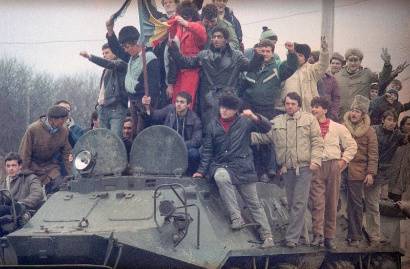 People at the armored carrier in the suburbs of Timisoara, Romania,  while the fights between army and pro-Ceausescu forces on Saturday, Dec. 23, 1989.  It is reported that over 5000 people were killed in Timisoara during this week. (AP Photo/Dusan Vranic)