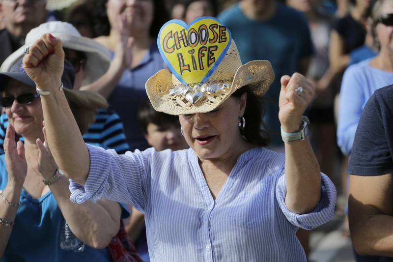Kathy Calver cheers for a speaker as she and other anti-abortion activists rally on the steps of the Texas Capitol to condemn the use in medical research of tissue samples obtained from aborted fetuses, Tuesday, July 28, 2015, in Austin, Texas. (AP Photo/Eric Gay)