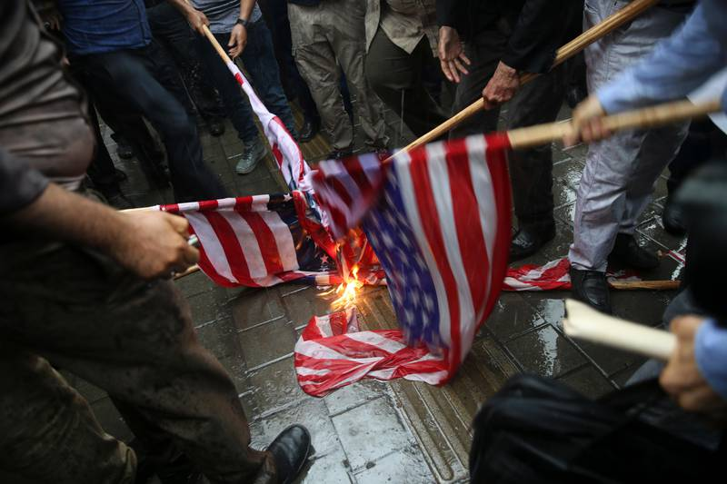 FILE - In this Wednesday, May 9, 2018 file photo, Iranian demonstrators burn representations of the U.S. flag during a protest in front of the former U.S. Embassy in response to President Donald Trump's decision to pull out of the nuclear deal and renew sanctions, in Tehran, Iran. There may not be much Iran can do about Trump?Äôs withdrawal from the nuclear deal, but across the Middle East, the Islamic Republic has a variety of ways it can hit back at the United States and America?Äôs regional allies. (AP Photo/Vahid Salemi)