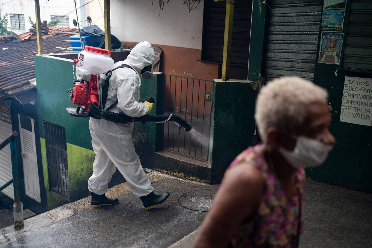 Thiago Firmino sprays disinfectant on an alley to avoid the spread the new corona virus at Santa Marta slum in Rio de Janeiro, Brazil, Friday, April 10, 2020. Firmino, who works as a tourist guide in the favela, helped organize a group to buy sanitization equipment with donated funds and are now disinfecting the alleyways of the favela. (AP Photo/Leo Correa)