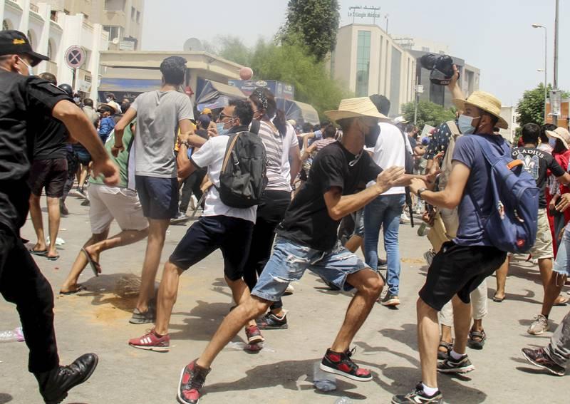 En tunisisk politimann jager vekk demonstranter langs gatene i Tunis søndag. Foto: Hassene Dridi / AP / NTB