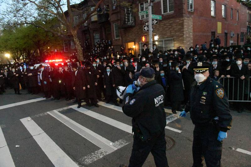 """Police instruct a crowd as hundreds of mourners gather in the Brooklyn borough of New York, Tuesday, April 28, 2020, to observe a funeral for Rabbi Chaim Mertz, a Hasidic Orthodox leader whose death was reportedly tied to the new coronavirus. The stress of the coronavirus' toll on the city's Orthodox Jews was brought to the fore Wednesday after Mayor Bill de Blasio chastised """"the Jewish community"""" following the breakup of the large funeral that flouted public health orders. (Todd Maisel via AP)"""