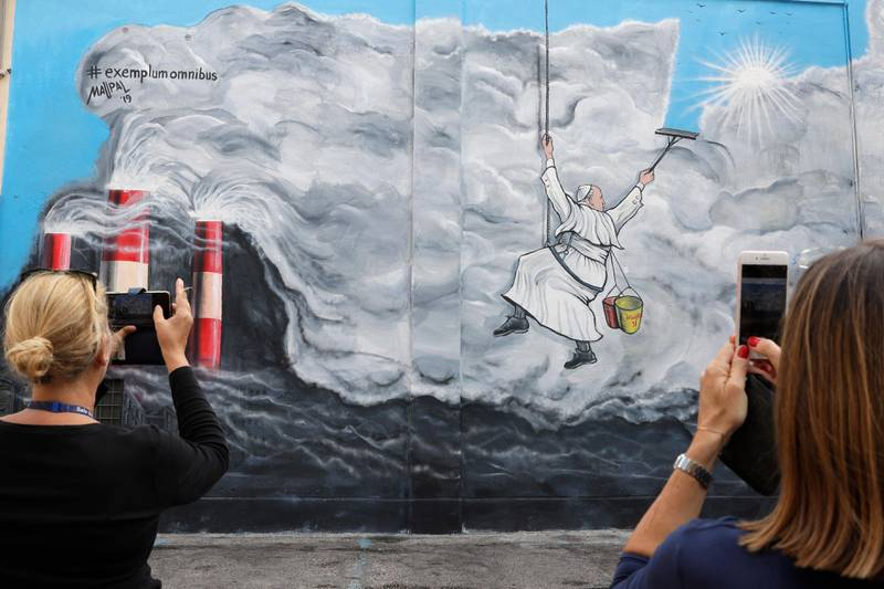 People photograph a graffiti depicting Pope Francis cleaning the sky from pollution, painted on a wall of Albano, near Rome, before the start of the pontiff visit, Saturday, Sept. 21, 2019. The graffiti realized by artist Maupal, Mauro Pallotta and named 'Exemplum Omnibus' (Example for All) was inspired by the encyclical 'Laudato Si' (Praise Be) where is declared an urgent need for the political and spiritual conversion of global leaders and individuals to dedicate themselves to curbing climate change and ending policies and personal habits that destroy creation. (AP Photo/ Andrew Medichini)