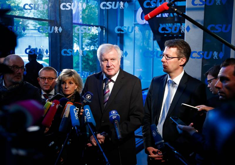 German Interior Minister and CSU chairman Horst Seehofer, center, and general secretary Markus Blume, right, answer questions at the headquarters of the Christian Social Union, CSU, in Munich, Germany, Monday, Oct. 15, 2018, the day after their party lost the absolute majority in Bavaria's state parliament by a wide margin. (AP Photo/Matthias Schrader)