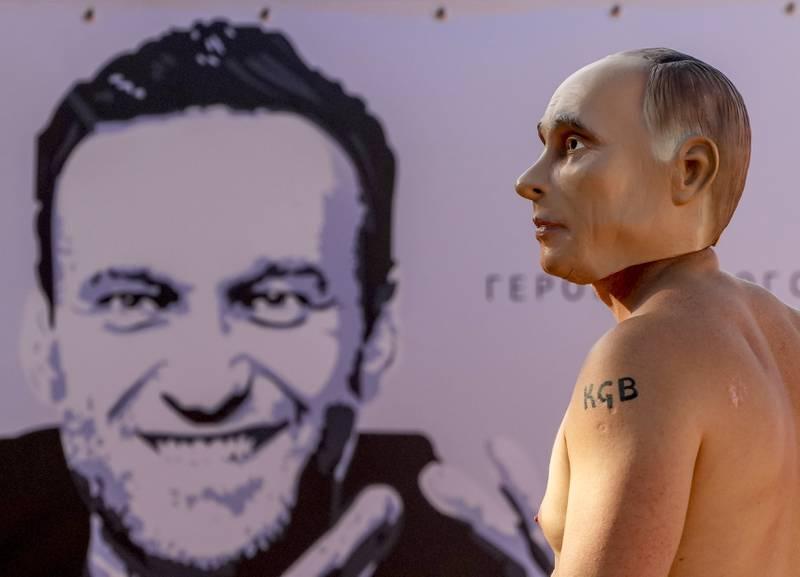 En mann med Putin-maske demonstrerer i Genève foran en plakat der Aleksej Navalnyj er avbildet. Foto: Michael Probst / AP / NTB
