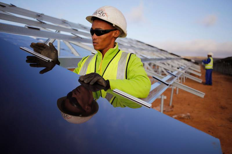 A worker installs a solar panel at a photovoltaic solar park situated on the outskirts of the coastal town of Lamberts Bay, South Africa, Tuesday, March. 29,  2016. Italian company TerniEnergia, started the solar park making use of a photovoltaic process that converts light into electricity through panels, with the facility expected to produce up to 75 Megawatts, to be connected to the South African electric grid. (AP Photo/Schalk van Zuydam)