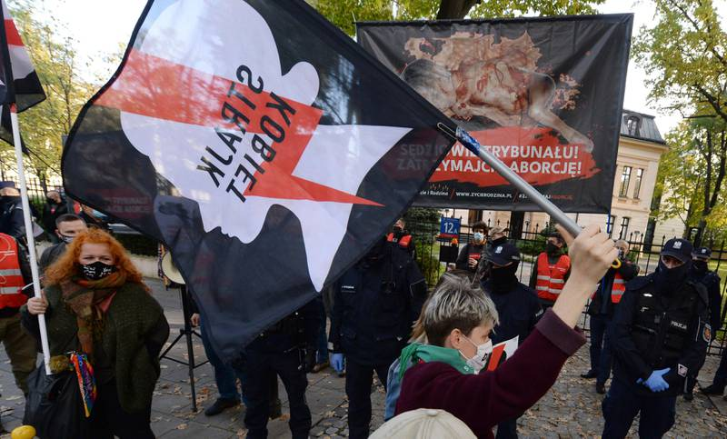 """Pro-choice activists from """"Women Strike"""" attend a protest in front of Poland's constitutional court, in Warsaw, Poland, Thursday, Oct. 22, 2020. Poland's top court has ruled that a law allowing abortion of fetuses with congenital defects is unconstitutional. The decision by the country's Constitutional Court effectively bans terminating pregnancies in cases where birth defects are found and will further limit access to abortions in Poland. (AP Photo/Czarek Sokolowski)"""