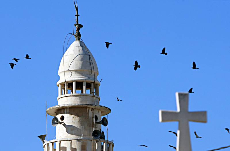 Birds fly around the minaret of a mosque and the cross atop a church in the northern West Bank village of Zababdeh, near Jenin, Monday, Dec. 23, 2013.  (AP Photo/Mohammed Ballas)