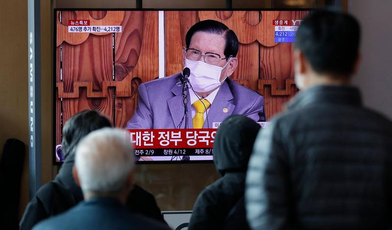 """People watch a TV screen showing a live broadcast reporting about Lee Man-hee, a leader of Shincheonji Church of Jesus, at the Seoul Railway Station in Seoul, South Korea, Monday, March 2, 2020. In the hastily arranged news conference Lee, the 88-year-old leader of a religious sect which has the country's largest cluster of infections, bowed down on the ground twice and apologized for causing the """"unintentional"""" spread of the disease. (AP Photo/Lee Jin-man)"""