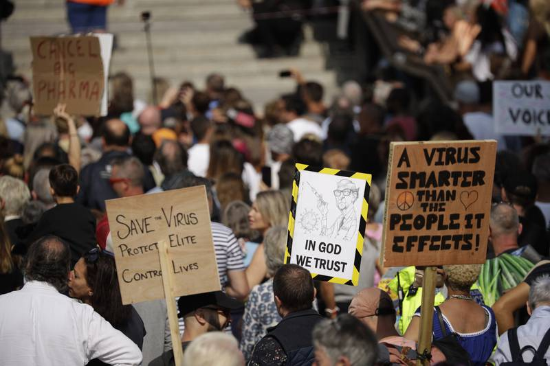 """People hold placards including one portraying Bill Gates as they take part in a """"Resist and Act for Freedom"""" protest against a mandatory coronavirus vaccine, wearing masks, social distancing and a second lockdown, in Trafalgar Square, London, Saturday, Sept. 19, 2020. (AP Photo/Matt Dunham)"""