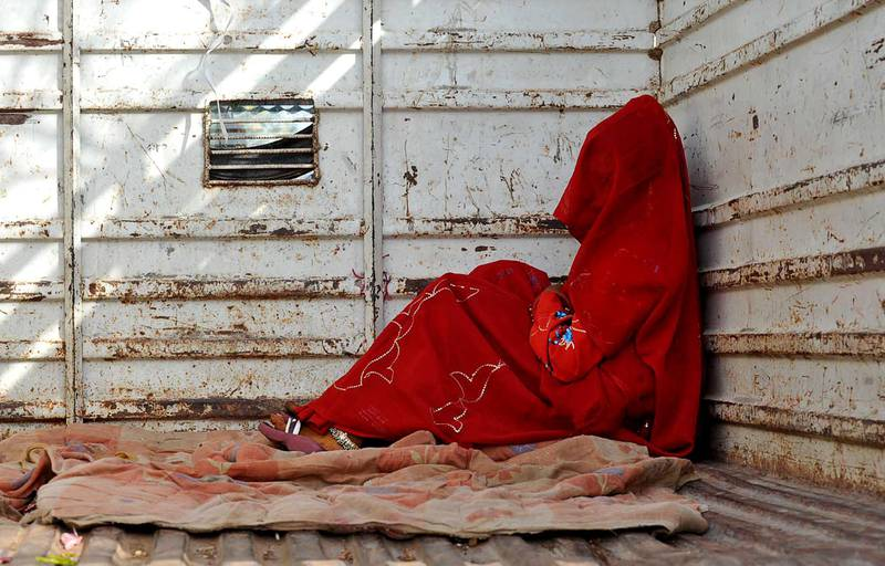 7-year-old child bride Guddu Bai sits at the back of a truck as she waits for the rest of her family members after being wed, at Biaora, about 135 kilometers from Bhopal, India, Saturday, May 7, 2011. Ignoring laws that ban child marriages, young children are still married off as part of centuries-old custom in some Indian villages. India law prohibits marriage for women younger than 18 and men under age 21. (AP Photo/Prakash Hatvalne)