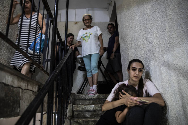 Folk som bor i den israelske byen Ashdod, søker beskyttelse i en trappeoppgang etter at alarmen gikk om et nytt rakettangrep fra Gaza. Foto: Heidi Levine / AP / NTB