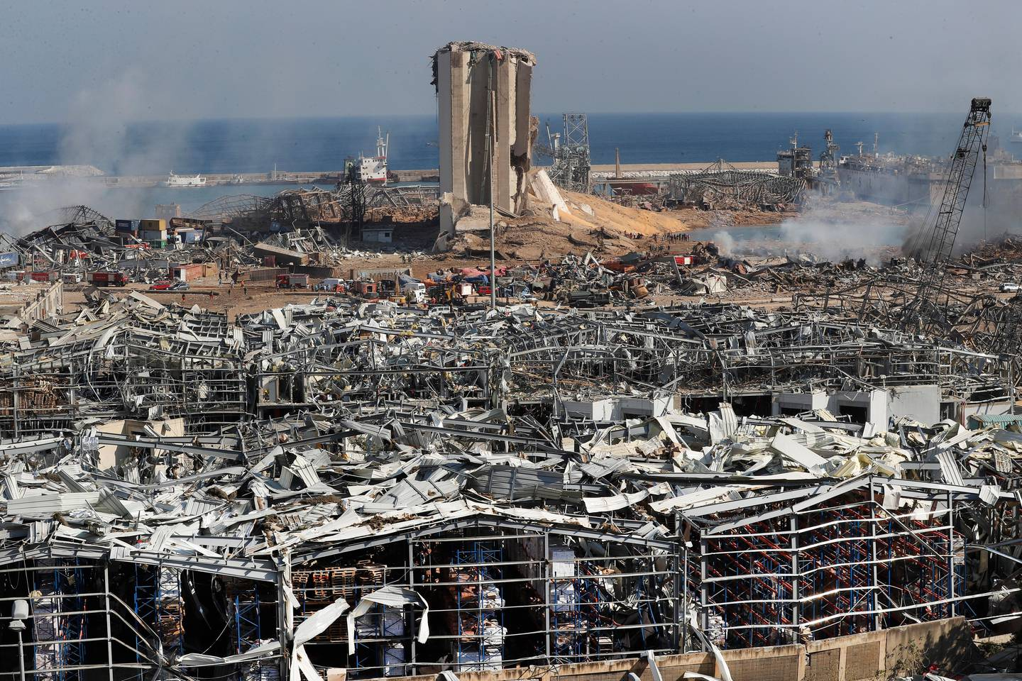 """Rescue workers and security officers work at the scene of an explosion that hit the seaport of Beirut, Lebanon, Wednesday, Aug. 5, 2020. Prime Minister Hassan Diab, in a short televised speech, has appealed to all countries and friends of Lebanon to extend help to the small nation, saying: """"We are witnessing a real catastrophe."""" (AP Photo/Hussein Malla)"""