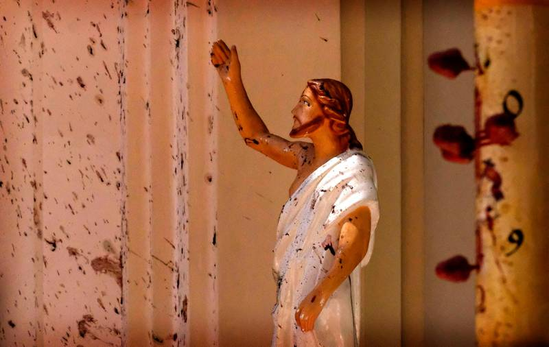 Blood stains are seen on the wall and on a Jesus Christ statue at the St. Sebastian's Church after blast in Negombo, north of Colombo, Sri Lanka, Sunday, April 21, 2019. More than hundred were killed and hundreds more hospitalized with injuries from eight blasts that rocked churches and hotels in and just outside of Sri Lanka's capital on Easter Sunday. (AP Photo)