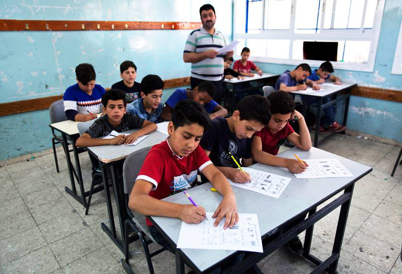 In this May 26, 2019 file photo, a teacher supervises while Palestinian school children attend a final exam during the last day of the school year, at the United Nations Relief and Works Agency for Palestine Refugees in the Near East, UNRWA, Hebron Boys School, in the West Bank city of Hebron. The head of the U.N. agency that helps 5.3 million Palestinian refugees says it is mobilizing to replenish a $211 million shortfall in the face of U.S. funding cuts. Pierre Kraehenbuehl said Monday, June 17, 2019, in Jordan that UNRWA will start running out of money if it does not receive significant commitments at its pledging conference next week (AP Photo/Nasser Nasser, File)