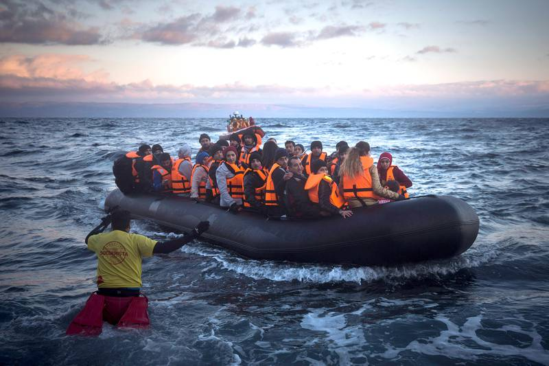 Refugees and migrants arrive on a dinghy from the Turkish coast to the Greek island of Lesbos, Friday, Dec. 18, 2015. European Union leaders on Thursday set a six-month deadline for deciding whether to push ahead with plans for a border guard agency that could deploy to member states unable or unwilling to manage their borders as thousands of migrants continue to arrive in Europe daily. (AP Photo/Santi Palacios)