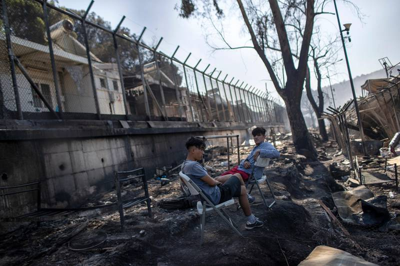Two young migrants sit next to the burned debris in the Moria refugee camp on the northeastern Aegean island of Lesbos, Greece, on Wednesday, Sept. 9, 2020. A major overnight fire swept through Greece's largest refugee camp, that had been placed under COVID-19 lockdown, leaving more than 12,000 migrants in emergency need of shelter on the island of Lesbos. (AP Photo/Petros Giannakouris)