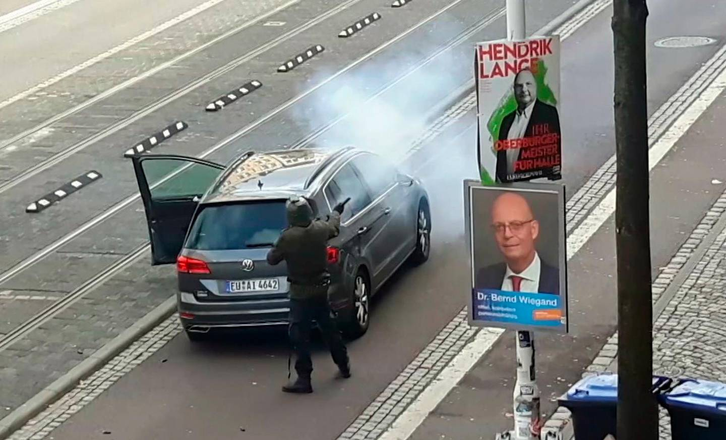 In this image taken from video made available by ATV-Studio Halle, a man shoots from long-barrelled gun, in Halle, Germany, Wednesday Oct. 9, 2019. A heavily armed assailant ranting about Jews tried to force his way into a synagogue in Germany on Yom Kippur, Judaism's holiest day, then shot two people to death nearby in an attack that was livestreamed on a popular gaming site. (ATV-Studio via AP)