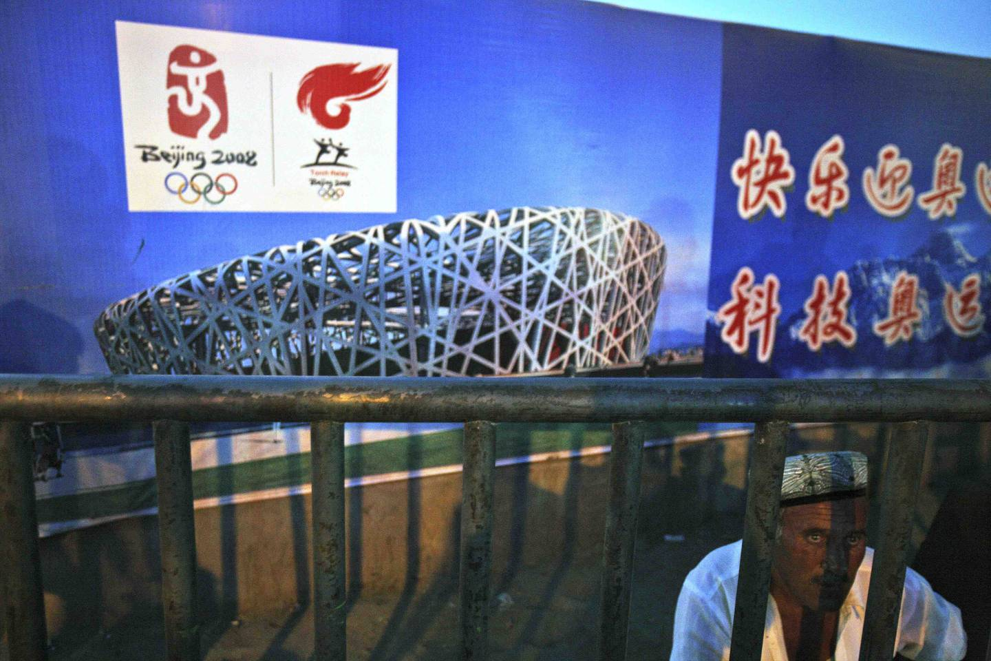 A Uighur pedlar waits for customers near a Beijing Olympics billboard showing the Bird Nest National Stadium in Kashgar, western China's Xinjiang province, Tuesday, Aug. 5, 2008. The attack by two Uighurs, a mainly Muslim ethnic minority group, killing 16 police on Monday triggered a full security alert in the restive Muslim territory just days before the Olympic Games. (AP Photo/Ng Han Guan)