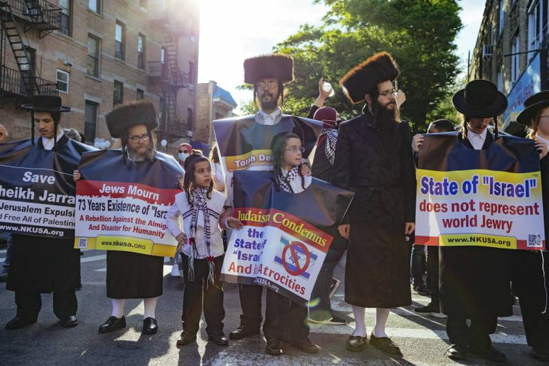 Orthodox Jewish men hold anti-Israel signage as thousands of activists supporting Palestine converge Saturday, May 15, 2021, in New York. The rally supports Palestine in the ongoing conflict between Israel and Palestine on the day Israeli airstrikes leveled several buildings in the Gaza strip. (AP Photo/Kevin Hagen)