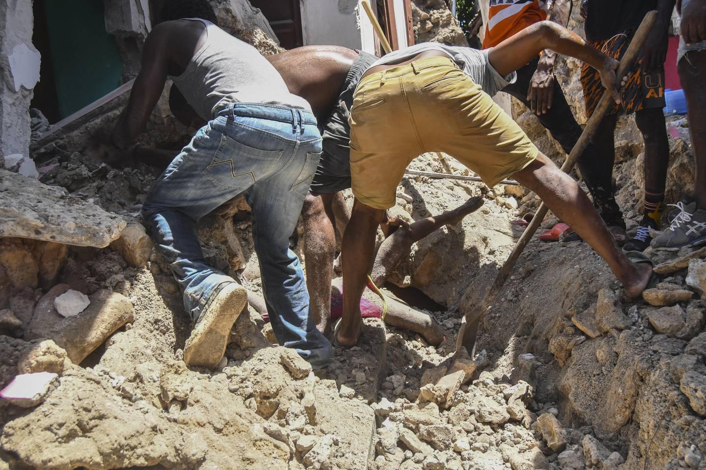 Menn jobber febrilsk for å redde en ung jente som er begravd i ruinene av et hus i Les Cayes etter et jordskjelv i Haiti. Foto: Duples Plymouth / AP / NTB