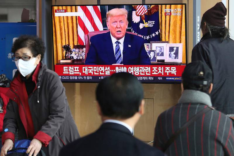 """People watch a TV screen showing a live broadcast of U.S. President Donald Trump's speech at the Seoul Railway Station in Seoul, South Korea, Thursday, March 12, 2020. Trump announced he is cutting off travel from Europe to the U.S. and moving to ease the economic cost of a viral pandemic that is roiling global financial markets and disrupting the daily lives of Americans. The Korean letters read: """"Trump national speech."""" (AP Photo/Ahn Young-joon)"""